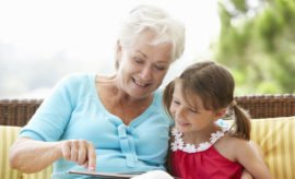 Grandmother And Granddaughter Reading Book On Garden Seat