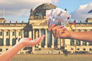 Reichstag und Hände, die Geld reichen
