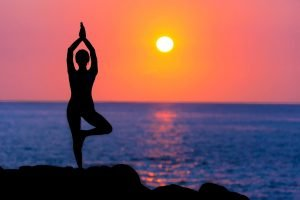 Frau macht abends am Meer Yoga