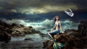 Meerjungfrau sitzt am Meer