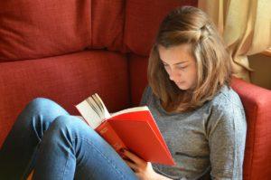 Mädchen liest auf Couch