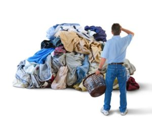 Man with laundry basket and huge pile of clothes