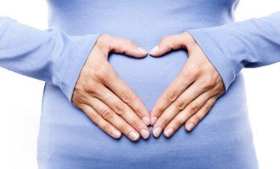 Frau hat Hände vor dem Bauch