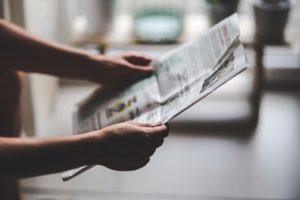 Zeitung in der Hand einer Person