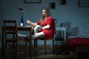Frau im roten Kleid sitzt in einem Zimmer