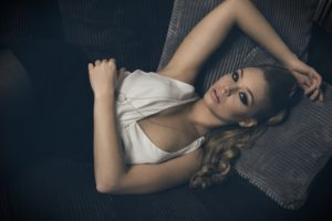 beautiful woman , in fashion portrait , she is laying on a sofa i her living room , has blond long hair , and looking wth a dream expression