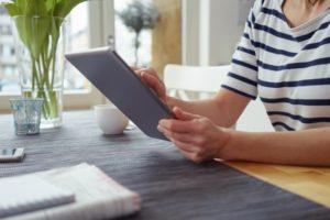 frau sitzt mit dem tablet am küchentisch