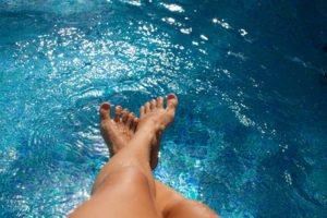 Woman lgs in swimming pool. Tanned feet with pedicure in the pool water.