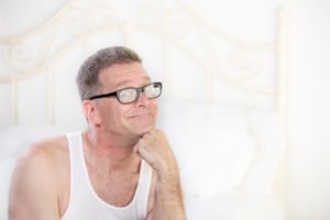 Handsome retro style man with glasses on a white bed